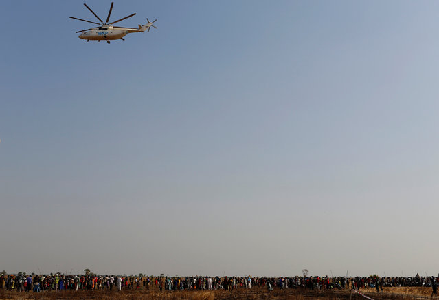 A United Nations World Food Programme (UN WFP) helicopter flies over a queue of people waiting to be registered prior to a food distribution in Thonyor, Leer county, South Sudan, February 25, 2017. (Photo by Siegfried Modola/Reuters)