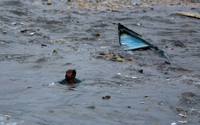 A fisherman swims to shore after his boat capsized due to high waves ahead of the expected landfall of Cyclone Vayu at Veraval, India, June 12, 2019. (Photo by Amit Dave/Reuters)