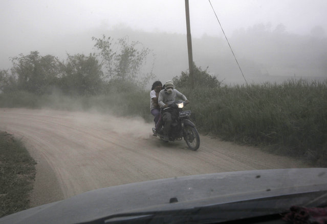 Motorists ride on a road covered in volcanic ash from the eruption of Mount Sinabung, in Tiga Pancur, North Sumatra, Indonesia, Saturday, June 13, 2015. The volcano, which was put on it highest alert level last week, has sporadically erupted since 2010 after being dormant for 400 years. (AP Photo/Binsar Bakkara)