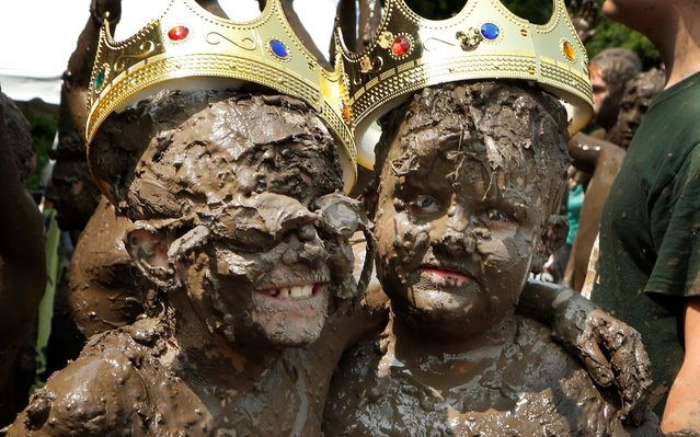 Mud Day Queen Riley Tulgetske, left, embraces Mud Day King Phoenix Crowder during Mud Day at the Nankin Mills Park, Tuesday, July 9, 2019, in Westland, Mich. The annual day is for kids 12 years old and younger. While parents might be welcome, this isn't an event meant for teens or adults. It's all about the kids having some good, unclean fun during their summer break and is sponsored by the Wayne County Parks. (Photo by Carlos Osorio/AP Photo)
