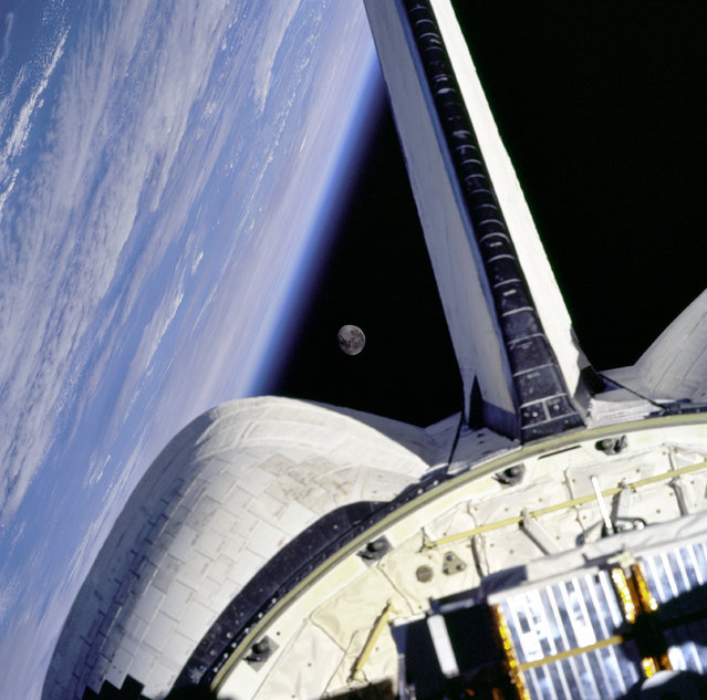 Earth and its moon are nicely framed in this image taken from the aft windows of the Space Shuttle Discovery in 1998. (Photo by NASA)