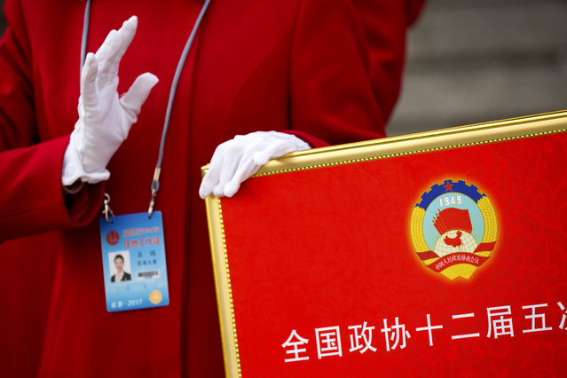 In this Friday, March 3, 2017 photo, a hospitality staff member holds a signboard with the logo of the Chinese People's Political Consultative Congress (CPPCC) as she directs delegates after the end of the opening session of the CPPCC at the Great Hall of the People in Beijing. (Photo by Mark Schiefelbein/AP Photo)