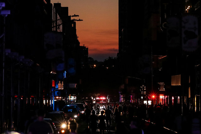People walk along a dark street near Times Square area, as a blackout affects buildings and traffic during widespread power outages in the Manhattan borough of New York, U.S, July 13, 2019. (Photo by Jeenah Moon/Reuters)