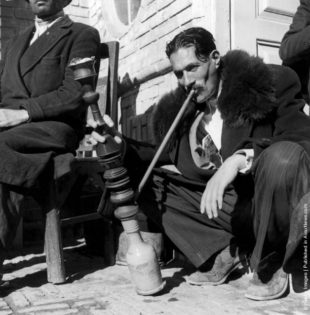 1955:  An Iranian smokes a Persian hookah or  water pipe on the pavement in Isafahan. The pipe is hired by a specialist merchant for single use