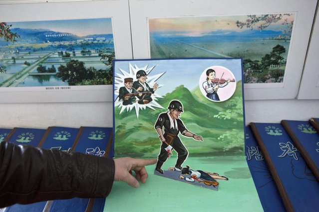 A North Korean teacher holds open a children's pop-up book, which depicts a U.S. soldier killing a Korean woman with a hatchet, in a library room at Kaeson Kindergarten in central Pyongyang on Saturday, March 9, 2013. For North Koreans, the systematic indoctrination of anti-Americanism starts as early as kindergarten. (Photo by David Guttenfelder/AP Photo)