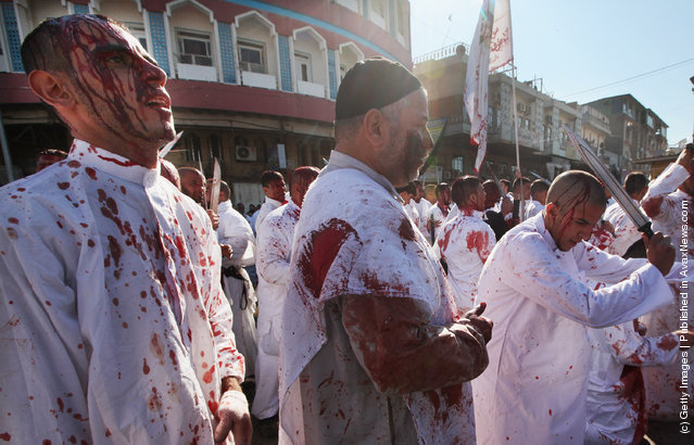 A Shi'ite worshiper (R) cuts his scalp as others bleed after cutting their scalps in a ritual display of mourning during an Ashura commemoration ceremony outside Kadhimiya shrine in Baghdad, Iraq