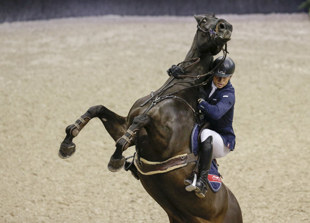 Austria's Max Kuhner hangs on to his horse Cornet Kalua, who balked at a jump in the FEI World Cup equestrian jumping speed class in Omaha, Neb., Thursday, March 30, 2017. (Photo by Nati Harnik/AP Photo)