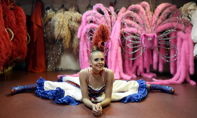 """A dancer of the Moulin Rouge cabaret stretches prior to a show on April 22, 2014 in Paris. Since 1945, the """"Maison Clairvoy"""" is specialised in the creation of luxury shoes and started in 1960 a collaboration with the famous Moulin Rouge to create boots and shoes for French Cancan dancers. (Photo by Franck Fife/AFP Photo)"""