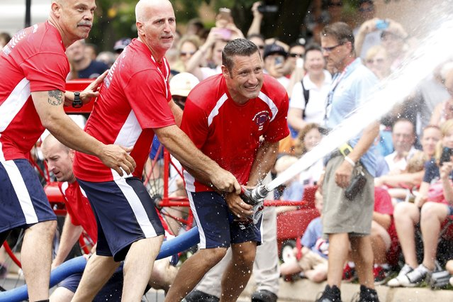 Members of the Indianapolis team knock down a target with a fire hose during the hose cart competition of the Firefighter Muster event at the World Fire and Police Games in Fairfax, Virginia July 4, 2015. (Photo by Jonathan Ernst/Reuters)