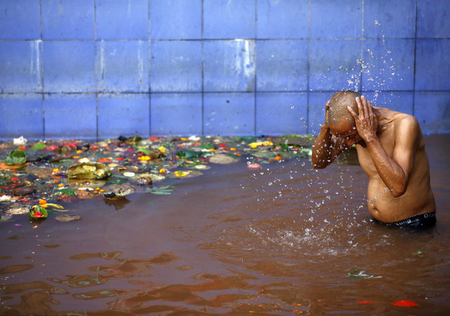 A devotee takes a holy bath at Matathirtha to commemorate his departed mother during Mother's Day in Kathmandu, Nepal, May 6, 2016. (Photo by Navesh Chitrakar/Reuters)