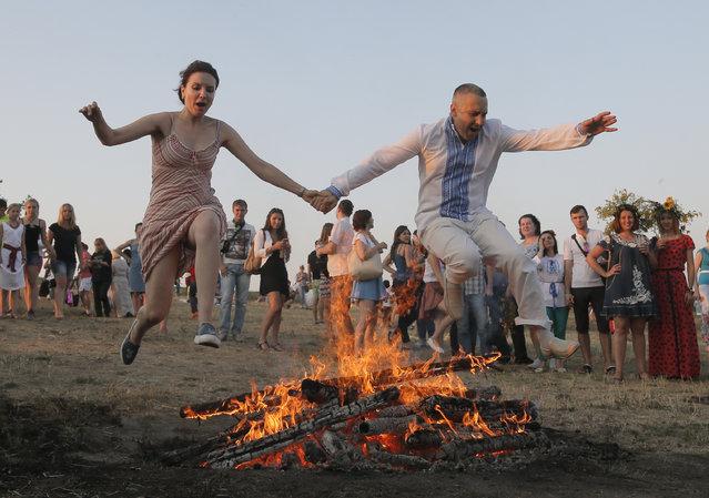 A Ukrainian couple jump over a fire during a traditional Midsummer Night celebration near Kiev, Ukraine, late Monday, July 6, 2015. (Photo by Efrem Lukatsky/AP Photo)