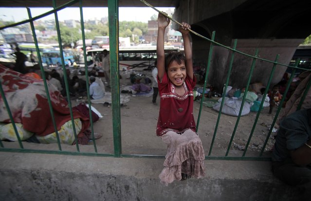 A homeless Indian girl plays hangs on a railing near her temporary home under a flyover in Jammu, India, Friday, May 2, 2014. Some 800 million people in the country live in poverty, many of them migrating to big cities in search of a livelihood and often ending up on the streets. (Photo by Channi Anand/AP Photo)