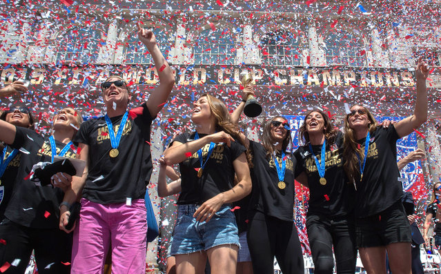 In a flurry of confetti, Abby Wambach, third from left, gestures to the crowd, surrounded by her teammates during a celebration for the U.S. Women's World Cup soccer champions at New York's City Hall, following their ticker tape parade up Broadway's Canyon of Heroes, Friday July 10, 2015. (Photo by Bryan R. Smith/AP Photo)