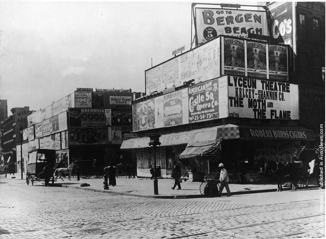 View of the intersection of Broadway and 42nd Streets, with a cigar store, horsedrawn carriages and advertisements, New York City, 1900