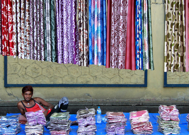 A vendor selling curtains waits for customers on a footpath along a road in Kochi, April 13, 2017. (Photo by Sivaram V/Reuters)