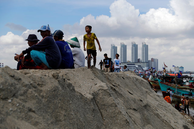 A group of fishermen sit on reclaimed land during a protest against reclamation in Jakarta Bay, Indonesia, April 17, 2016. (Photo by Reuters/Beawiharta)