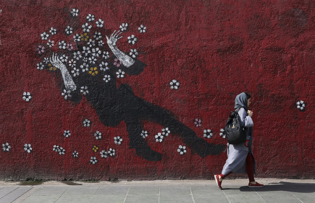 A woman walks past a mural in a sidewalk in downtown Tehran, Iran, Sunday, July 21, 2019. (Photo by Vahid Salemi/AP Photo)
