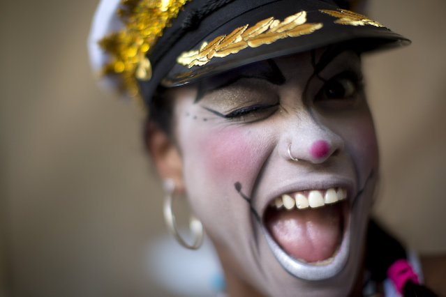 "A woman smiles for a photo at the ""Carnaval na Central"" carnival block parade, in central station, during pre-carnival celebrations in Rio de Janeiro, Brazil, Saturday, February 2, 2013. (Photo by Felipe Dana/AP Photo)"