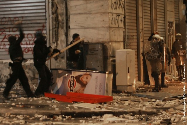 Demonstrators throw projectiles at riot police during violent protests on February 12, 2012 in Athens, Greece