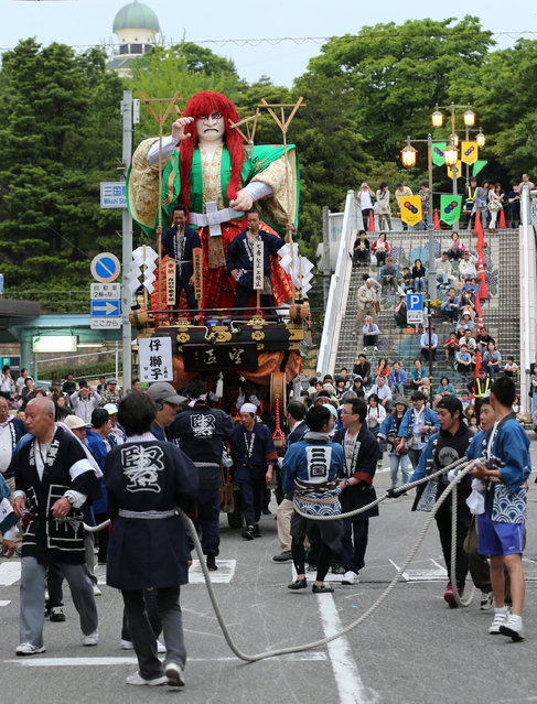 Festival goers pull huge paper doll of historical Japanese figure named Ko-shishi on the carts during the Mikuini annual festival on May 20, 2014 in Sakai, Japan. The annual festival takes place from May 19-21 and is attended by thousands of visitors. During the festival people dressed in traditional Japanese costumes pull carts carrying 6 meter high dolls of Japanese historical figures through the narrow streets. The origins of the festival are unclear but its history can be traced back more than 250 years. (Photo by Buddhika Weerasinghe/Getty Images)