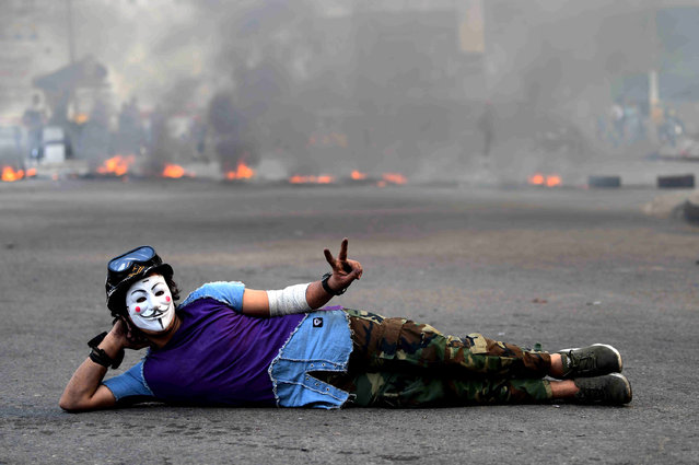 An Iraqi protester wearing a Guy Fawkes mask flashes victory signs in front a fire set by protesters to block a street during a protest and strike at Khillani square in central Baghdad, Iraq, 03 November 2019. Thousands of Iraqi teachers and university students participated in a strike and hundreds of protesters closed the roads in Baghdad as part of the wave of protests across the country, against the Iraqi government corruption, in response to the call of Iraqi Teachers Union and activists. (Photo by Murtaja Lateef/EPA/EFE)