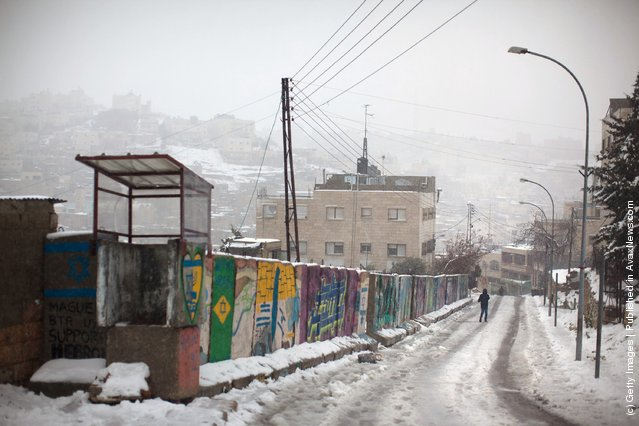 A man walks down a hill as snow falls on March 2, 2012 in Hebron, West Bank