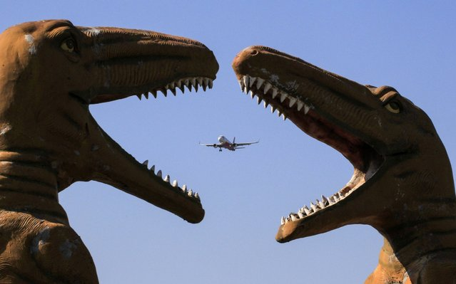"An aircraft flies past sculptures of dinosaurs at the ""Valley of Animals"" park in Chandigarh, India on November 9, 2019. (Photo by Vijay Mathur/AFP Photo)"