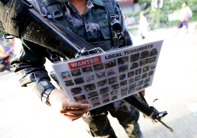 """A police officer holds a poster of wanted Filipino Muslim militants known as """"Maute"""" group at a checkpoint set up at the entrance to Iligan city Saturday, May 27, 2017 in southern Philippines. Iligan city is one of the safe havens for the tens of thousands of Marawi residents who have fled their city following the rampage by Muslim militants. (Photo by Bullit Marquez/AP Photo)"""