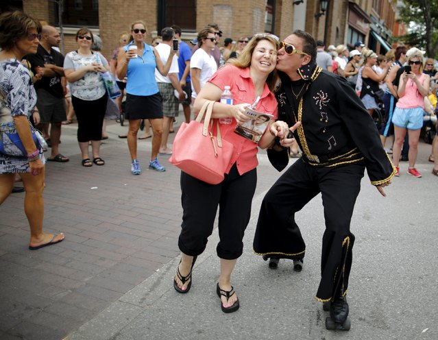 "Elvis Presley tribute artist ""Fast Eddie the Roller Skating Elvis"" of Orillia, Ontario kisses a fan during the four-day Collingwood Elvis Festival in Collingwood, Ontario July 25, 2015. (Photo by Chris Helgren/Reuters)"