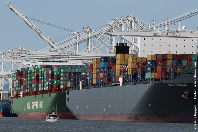 The container ship MSC Fabiola (R) is seen docked at the Port of Oakland on March 22, 2012, in Oakland, California