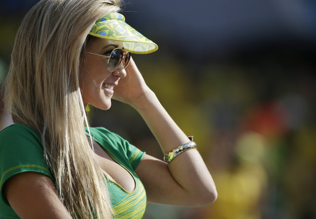 A Brazil fan waits for the start of the group A World Cup soccer match between Brazil and Croatia, the opening game of the tournament, in the Itaquerao Stadium in Sao Paulo, Brazil, Thursday, June 12, 2014. (Photo by Felipe Dana/AP Photo)