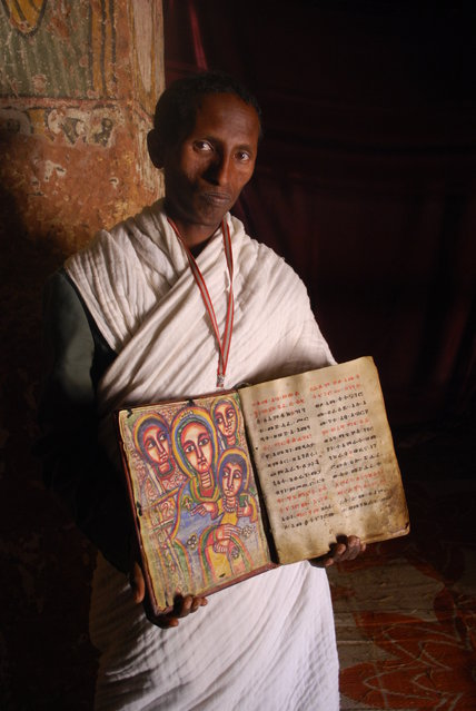 """The gate keeper"". It was a bit nerve wracking getting to the top of the church, but so worth it. The book being held is extremely old, and the images were stunning. Photo location: Abuna Yemata Guh church, Ethiopia. (Photo and caption by Kristen Eder/National Geographic Photo Contest)"
