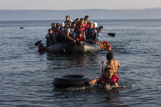 Two migrants pull an overcrowded dinghy with Syrian and Afghan refugees arriving from the Turkish coasts to the Greek island of Lesbos, Monday, July 27, 2015. Nearly 50,000 people have illegally entered the country this year, mostly Syrian refugees who risk the sea crossing from Turkey in dangerous, overcrowded boats. From Greece, most try to continue north through the Balkans to more affluent European countries such as Germany. (Photo by Santi Palacios/AP Photo)