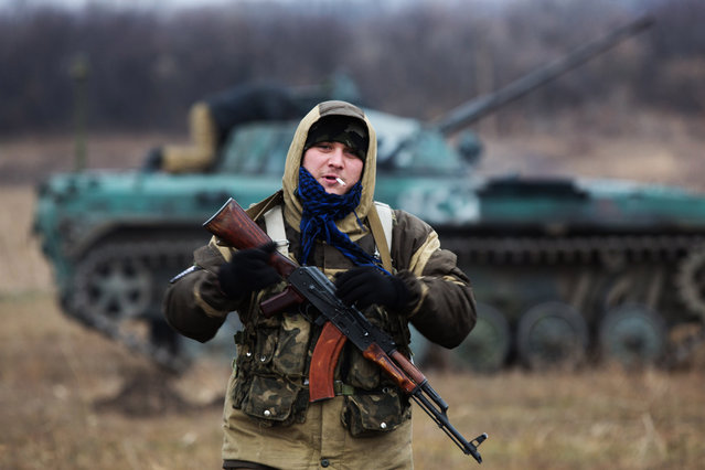 """A Pro-Russian militant holds a Kalachnikov asssault rifle and smokes a cigarette in front of a tank taken from Ukrainian forces during fighting in August, as he and other fire their weapons in an open field, in the eastern Ukrainian town of Ilovaisk, some 40 kms east of Donetsk, on November 18 2014. NATO warned on on Novemeber 18  of a """"very serious"""" build-up of Russian soldiers and weapons inside Ukraine and on its border as Germany's foreign minister urged Kiev and Moscow to respect a tattered peace plan. (Photo by Menahem Kahana/AFP Photo)"""