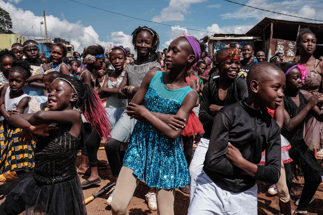 "Members of ""Project Elimu"" perform as a part of their presentation in a street of Kibera slum in Nairobi, Kenya, on December 14, 2019. Project Elimu is Kenyan Non-Profit Organization founded by former professional Kenyan dancer Mike Wamaya to provide wide range of extracurricular activities to schools within informal settlements to empower children and teachers as over 400 children from 25 different schools participate. (Photo by Yasuyoshi Chiba/AFP Photo)"