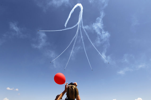 A woman watches as Latvia's Baltic Bees aerobatic team on L-39C Albatross airplanes, perform a maneuver during Bucharest International Air Show at Baneasa airport June 22, 2014. (Photo by Bogdan Cristel/Reuters)