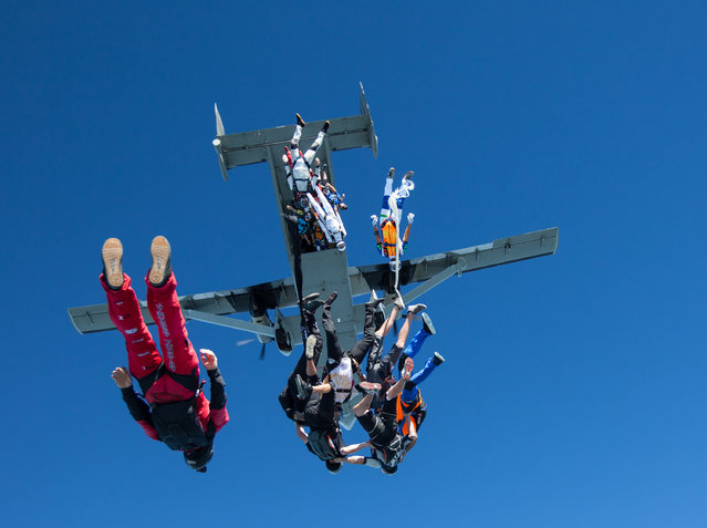 In this photo provided by Jason Peters, members of an international team of skydivers exit a jump plane, flying head-down on their way to building their world record skydiving formation, Friday, July 31, 2015, over Ottawa, Ill. It took the team 13 attempts to to build the formation, resembling a giant flower, to beat the 2012 mark set by 138 skydivers. (Photo by Jason Peters via AP Photo)