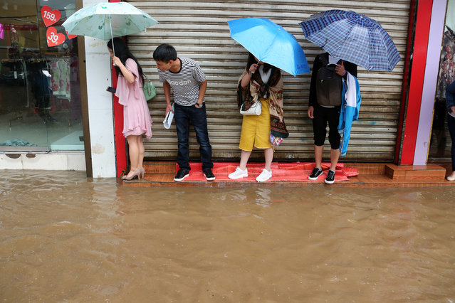 People stand by a flooded street in Weining County, southwest China's Guizhou Province, June 11, 2017. Heavy rain hit Guizhou since Sunday. (Photo by He Huan/Xinhua/Barcroft Images)