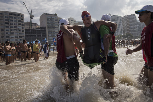 Krige Schabort of the United States, is carried out of the water at Copacabana Beach as he competes in the men's PT1 Paralympic Triathlon test event in Rio de Janeiro, Brazil, Saturday, August 1, 2015. (Photo by Felipe Dana/AP Photo)