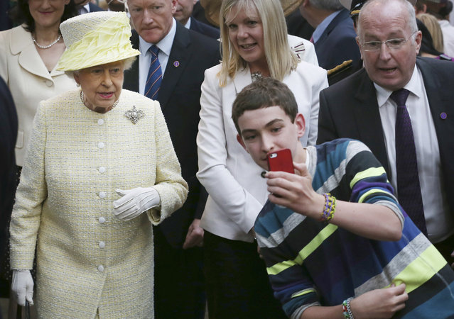 A local youth takes a selfie photograph in front of Queen Elizabeth II during a visit to St George's indoor market on  in Belfast Tuesday June 24, 2014. The Queen is on a 3 day visit to Northern Ireland . (Photo by Peter Macdiarmid/AP Photo)