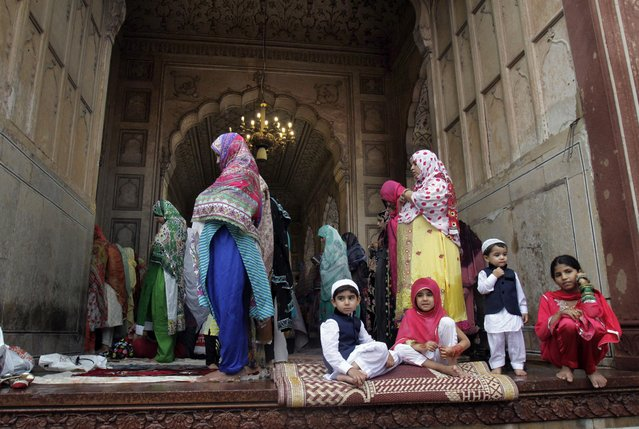 Pakistani children sit near to their mothers offering Eid al-Fitr prayers at historical Badshahi mosque in Lahore, Pakistan, Saturday, July 18, 2015. (Photo by K. M. Chaudary/AP Photo)