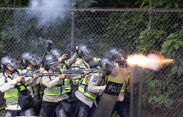 Riot police fire rubber bullets and tear gas grenades at students from the public Central University of Venezuela who  demonstrate in demand of the referendum on removing President Nicolas Maduro in Caracas on June 9, 2016. (Photo by Federico Parra/AFP Photo)