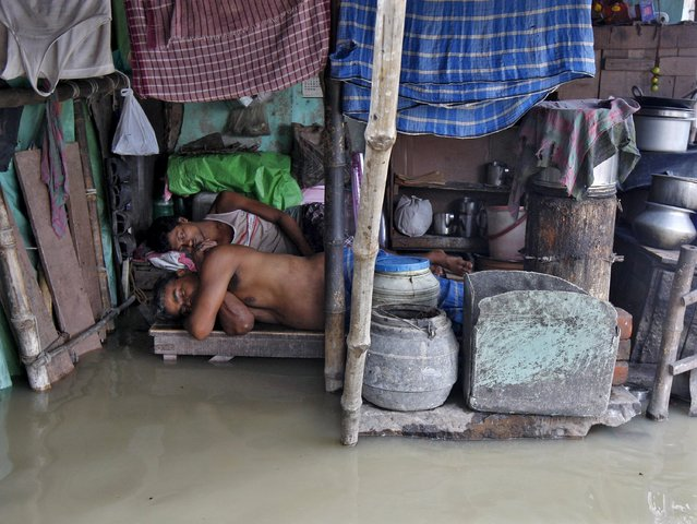Local residents sleep inside a flooded hut after heavy monsoon rains in the eastern India caused the rise in water levels of river Ganga and its tributaries in Kolkata, India, August 3, 2015. (Photo by Rupak De Chowdhuri/Reuters)