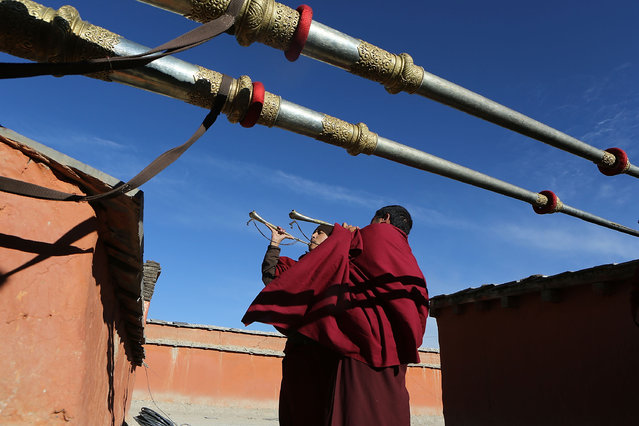 Monks play gyaling and dungchen, Tibetan ritual instruments, from a monastery rooftop at the end of a ceremony during the Tenchi Festival on May 24, 2014 in Lo Manthang, Nepal. The Tenchi Festival takes place annually in Lo Manthang, the capital of Upper Mustang and the former Tibetan Kingdom of Lo. Each spring, monks perform ceremonies, rites, and dances during the Tenchi Festival to dispel evils and demons from the former kingdom. (Photo by Taylor Weidman/Getty Images)
