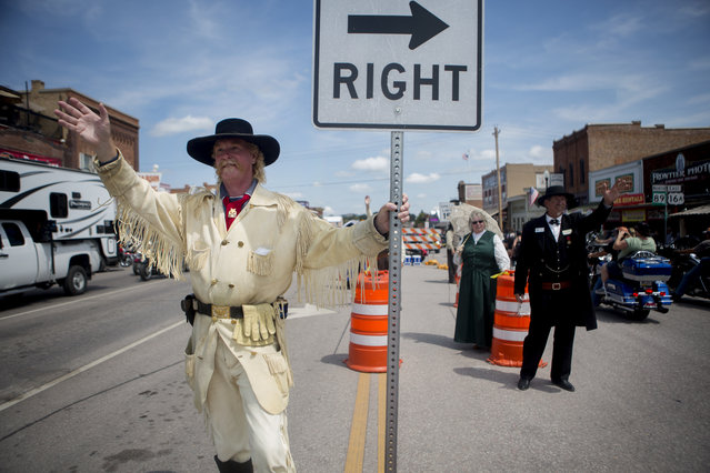 Mitch McLain, dressed as General George Custer, greets bikers entering downtown Custer during the annual Sturgis Motorcycle Rally in South Dakota, August 3, 2015. (Photo by Kristina Barker/Reuters)