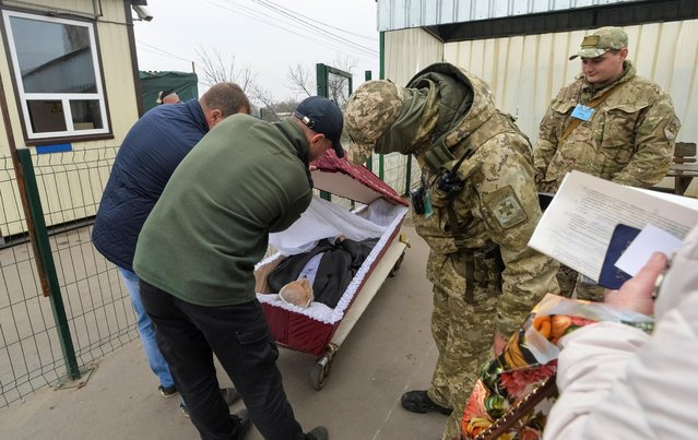 A serviceman inspects a coffin containing a deceased man being transported through a checkpoint from the self-proclaimed Luhansk People's Republic to Ukrainian government-controlled territory for his funeral in Stanytsia Luhanska settlement, October 24, 2019. (Photo by Oleksandr Klymenko/Reuters)