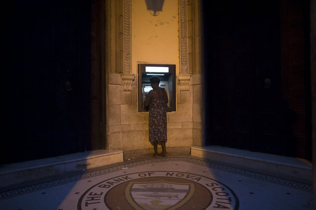 A woman uses an automated teller machine (ATM) in downtown Havana July 31, 2015. (Photo by Alexandre Meneghini/Reuters)