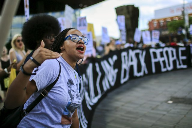 A protester shouts slogans against police while people take part in a rally at Barclays Center marking the first anniversary of the death of Michael Brown, in Brooklyn, New York August 9, 2015. (Photo by Eduardo Munoz/Reuters)