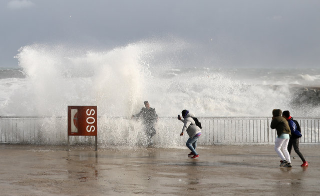 """Tourists take a pictures as sea waves cover them during the storm """"Gloria"""" on Barceloneta beach, in Barcelona, Spain, January 20, 2020. (Photo by Nacho Doce/Reuters)"""