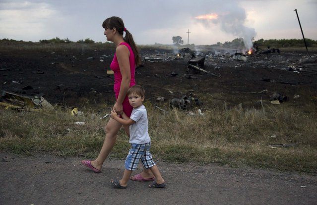 A woman with a child walks past the crash site of a passenger plane near the village of Grabovo, Ukraine, Thursday, July 17, 2014. Ukraine said a passenger plane carrying 295 people was shot down Thursday as it flew over the country, and both the government and the pro-Russia separatists fighting in the region denied any responsibility for downing the plane. (Photo by Dmitry Lovetsky/AP Photo)